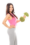 Attractive woman holding a broccoli dumbbell Royalty Free Stock Image
