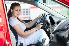 Attractive woman holding car wheel through opened door Stock Photos