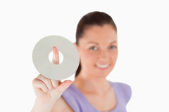 Attractive woman holding a CD while standing Royalty Free Stock Image