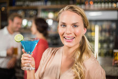 Attractive woman holding cocktail glass facing camera Royalty Free Stock Image