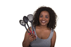 Attractive woman holding cooking utensils Stock Images