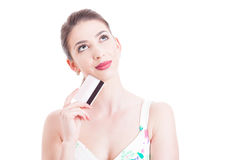 Attractive woman holding credit card and feeling pensive Royalty Free Stock Photo