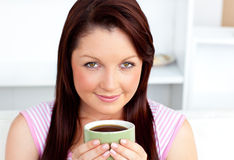 Attractive woman holding a cup of coffee at home Royalty Free Stock Photos