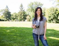 Attractive Woman Holding Digital Camera In Park Royalty Free Stock Images