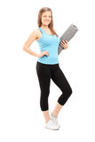 Attractive woman holding an exercise mat Royalty Free Stock Images