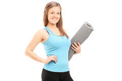 Attractive woman holding an exercise mat Royalty Free Stock Photography