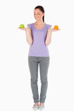 Attractive woman holding fruits while standing Stock Photo