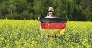 Attractive woman holding a German flag in a yellow rapeseed field. Flag of Germany fluttering in the wind stock footage