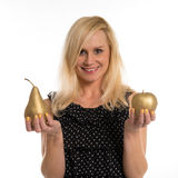 Attractive woman holding a golden pear and apple Royalty Free Stock Photo
