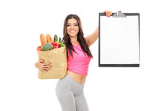 Attractive woman holding a grocery bag and a clipboard Stock Image