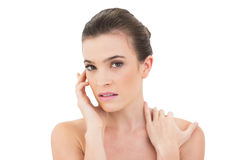 Attractive woman holding hand on face and shoulder Stock Photography