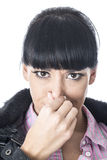Attractive Woman Holding Her Nose to Stop a Bad Smell or Aroma Royalty Free Stock Photography