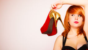 Attractive woman holding high heel shoes. Stock Photo