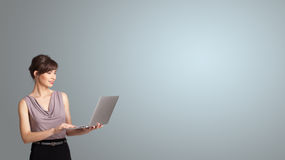 Attractive woman holding a laptop with copy space. Attractive young woman holding a laptop with copy space stock images