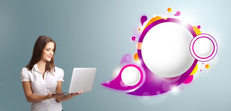 Attractive woman holding a laptop and presenting abstract speech. Attractive young woman holding a laptop and presenting abstract speech bubble copy space Stock Photo