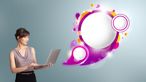 Attractive woman holding a laptop and presenting abstract speech. Attractive young woman holding a laptop and presenting abstract speech bubble copy space stock images