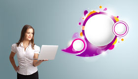 Attractive woman holding a laptop and presenting abstract speech. Attractive young woman holding a laptop and presenting abstract speech bubble copy space royalty free stock photos
