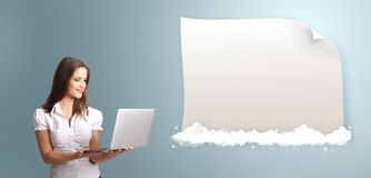 Attractive woman holding a laptop and presenting modern copy spa. Attractive young woman holding a laptop and presenting modern copy space on clouds royalty free stock photo