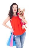 Attractive woman holding little dog yorkshire terrier and shopping bags isolated on white. Background stock photography