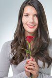 Attractive woman holding a long-stemmed red rose Royalty Free Stock Image