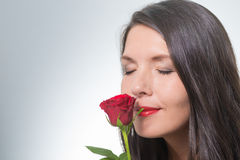 Attractive woman holding a long-stemmed red rose Stock Images