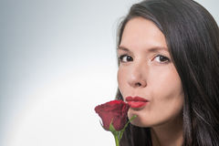 Attractive woman holding a long-stemmed red rose Royalty Free Stock Photo