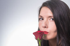 Attractive woman holding a long-stemmed red rose Royalty Free Stock Photos