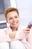 Attractive woman holding mobilephone. Attractive young woman holding mobile, smiling happy Stock Photos