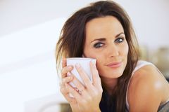 Attractive Woman Holding a Mug Close to Her Face Stock Photo
