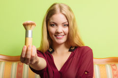 Attractive woman holding powder brush. Make up. Royalty Free Stock Image
