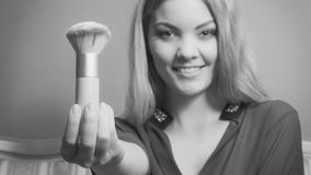 Attractive woman holding powder brush. Make up. Young attractive pretty woman girl holding powder brush. Fashion and make up. Black and white photo Royalty Free Stock Images