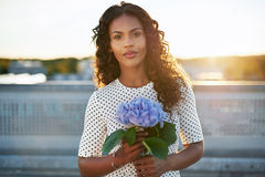Attractive woman holding a pretty flower Royalty Free Stock Photography