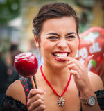 Attractive woman holding a red caramelized apple at the Oktoberfest Stock Image