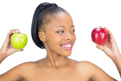 Attractive woman holding red and green apple looking at the red one Royalty Free Stock Photos