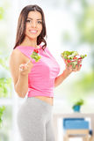 Attractive woman holding a salad at home Stock Photo