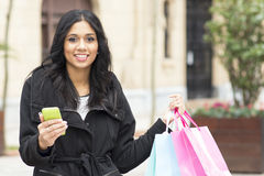 Attractive woman holding shopping bags and phone. Royalty Free Stock Photos