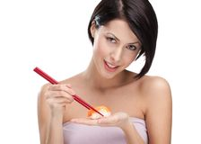Attractive woman holding sushi with a chopsticks Stock Photography