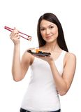 Attractive woman holding sushi roll Royalty Free Stock Photos