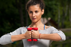 Attractive woman holding two weights together Royalty Free Stock Photo