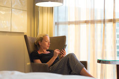 Attractive woman holding and using smart phone while sitting on armchair in modern hotel room. Stock Photos