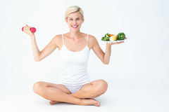 Attractive woman holding vegetables plate and dumbbell Stock Photography