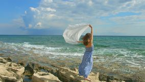 Attractive woman holding white scarf in wind on rocky shore. Freedom, happiness. Stock footage stock footage