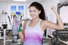 Attractive woman holds beverage at gym Stock Photo