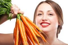 Attractive woman holds bunch of carrots Royalty Free Stock Photos
