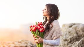 Attractive woman holds in hands a bunch of flowers stock photos