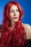 Attractive woman with huge red mane, blue chroma Stock Image
