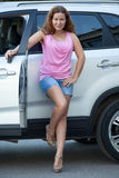 Attractive woman with ignition key standing near own suv, full-length Royalty Free Stock Image