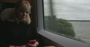 Attractive woman immersed in your phone on the train stock footage