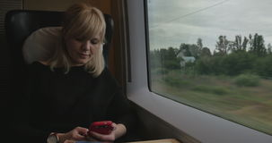 Attractive woman immersed in your phone on the train stock video footage