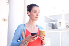 Attractive woman inside holding coffee and cellphone Royalty Free Stock Photos
